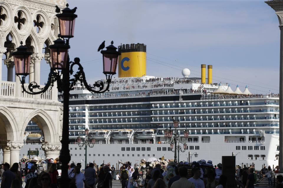 """FILE-- A cruise ship passes by St. Mark's Square filled with tourists, in Venice, Italy, Sunday, June 2, 2019. Declaring Venice's waterways a """"national monument,"""" Italy is banning mammoth cruise liners from sailing into the lagoon city, which risked within days being declared an imperiled world heritage site by the United Nations. Culture Minister Dario Franceschini said the ban will take effect on Aug. 1 and was urgently adopted at a Cabinet meeting on Tuesday. . (AP Photo/Luca Bruno)"""