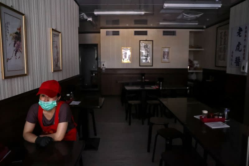 A restaurant staff member waits for the electricity to come back after an outage at a power plant, in Taipei