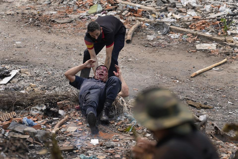 An officer comes to the aid of a fellow officer wounded in clashes during an Indigenous protest against a proposed bill that criminalizes land invasions, outside Congress in Asuncion, Paraguay, Wednesday, Sept. 29, 2021. If the bill passes it would affect several Indigenous communities who reside on improvised settlements pending the restitution of their lands. (AP Photo/Jorge Saenz)