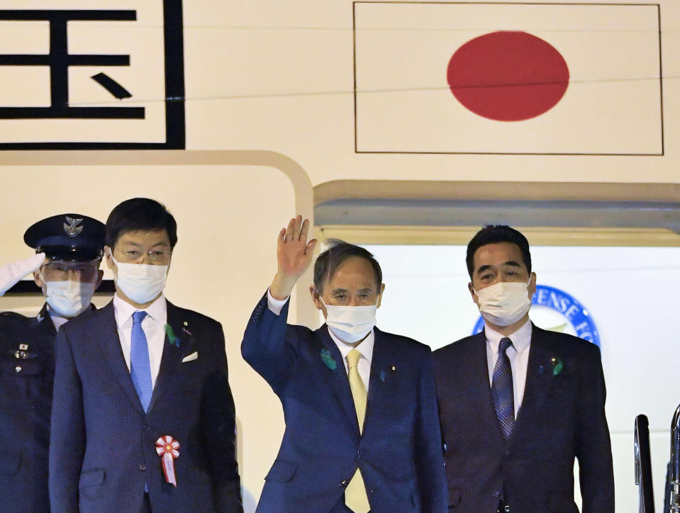 Japanese Prime Minister Yoshihide Suga, center, waves, on his departure for the U.S., at Haneda airport, in Tokyo Thursday, April 15, 2021. Suga headed to Washington on Thursday to become a first foreign leader to have a face-to-face meeting with President Joe Biden for talks that would reaffirm the strength of their alliance and how to deal with China's growing assertiveness and challenge to democratic values.(Kyodo News via AP)