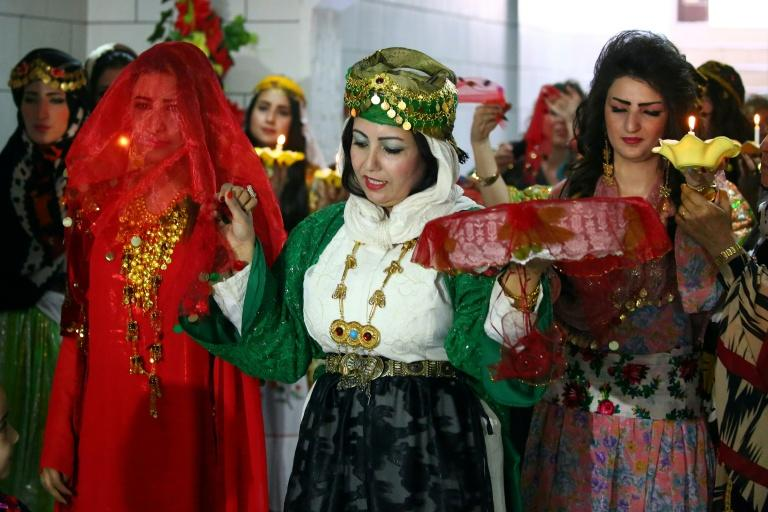 A Syrian-Kurdish fashion show culminates with the arrival of a model in a traditional bridal outfit: a red robe with a heavy gold necklace and a diaphanous red veil