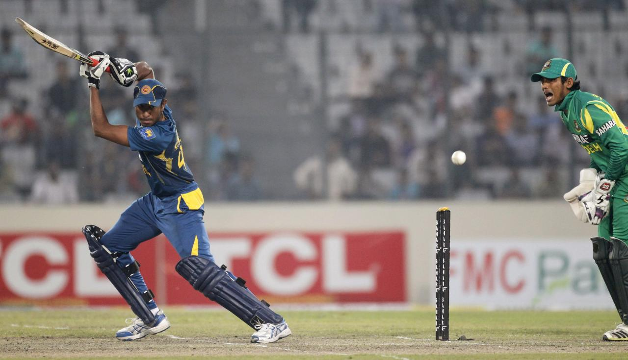 Sri Lanka's Kithuruwan Vithanage plays a shot as Bangladesh's wicketkeeper Anamul Haque (R) watches during their third one day international (ODI) cricket match of the series in Dhaka February 22, 2014. REUTERS/Andrew Biraj (BANGLADESH - Tags: SPORT CRICKET TPX IMAGES OF THE DAY)