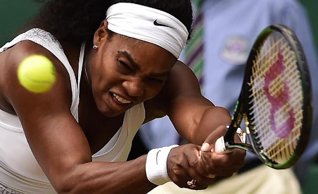 US player Serena Williams hits a return against her sister Venus Williams during their fourth round match at the Wimbledon Championships at The All England Tennis Club in southwest London, on July 6, 2015 (AFP Photo/Leon Neal)
