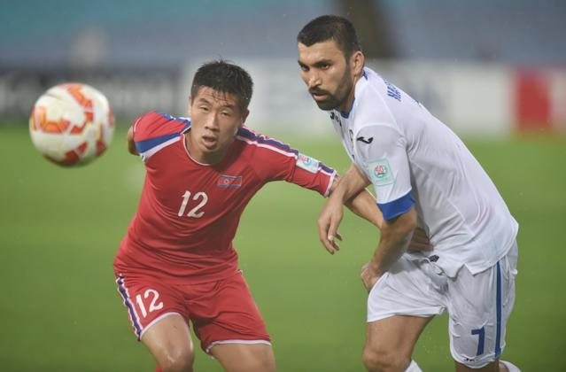Azizbek Haydarov of Uzbekistan (right) fights for the ball with Om Chol Song of North Korea during their Group B football match of the AFC Asian Cup in Sydney on January 10, 2015 (AFP Photo/Peter Parks)
