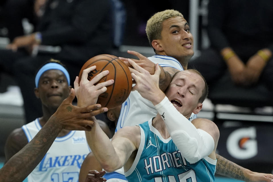Los Angeles Lakers forward Kyle Kuzma, top, vies for a rebound with Charlotte Hornets center Cody Zeller during the second half in an NBA basketball game on Tuesday, April 13, 2021, in Charlotte, N.C. (AP Photo/Chris Carlson)