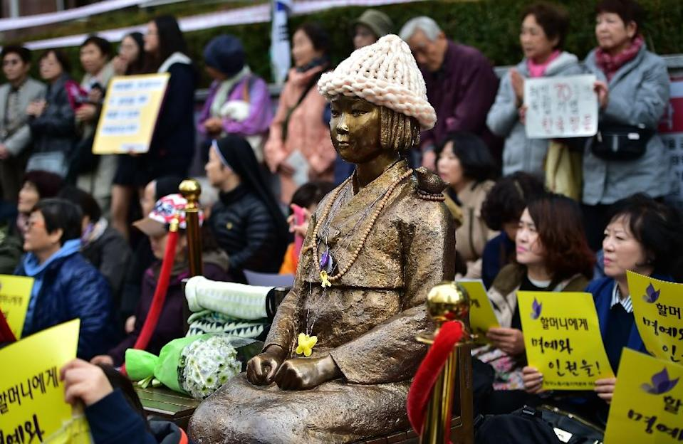 """Protestors in Seoul sit next to a statue of a South Korean teenage girl in traditional costume called the """"peace monument"""" for women used as sex slaves by Japanese soldiers during World War II (AFP Photo/Jung Yeon-Je)"""