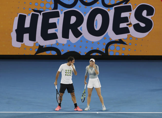 Denmark's Caroline Wozniacki and Switzerland's Roger Federer chat during the annual Kids Tennis Day event on Rod Laver Arena ahead of the Australian Open tennis championships in Melbourne, Australia Saturday, Jan. 13, 2018. (AP Photo/Ng Han Guan)