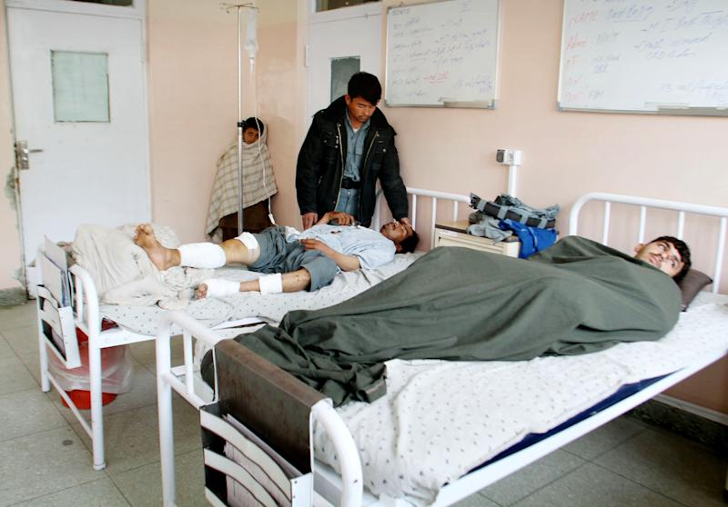 Victims of a roadside bomb lie on hospital beds after their truck was hit by roadside bomb in Kandahar, south of Kabul, Afghanistan, Sunday, Jan. 27, 2013. A police truck packed with officers and detainees struck a roadside bomb in southern Afghanistan's largest city, killing several of those aboard, officials said Sunday. (AP Photo/Allauddin Khan)