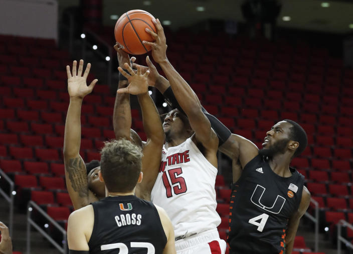 North Carolina State's Manny Bates (15) pulls in the rebound from Miami's Elijah Olaniyi (4) during the first half of an NCAA college basketball game at PNC Arena in Raleigh, N.C., Saturday, Jan. 9, 2021. (Ethan Hyman/The News & Observer via AP)