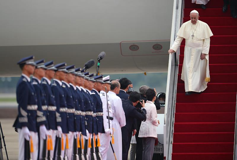 Pope Francis walks down the stairs of his plane upon his arrival in Seoul, August 14, 2014 (AFP Photo/Vincenzo Pinto)
