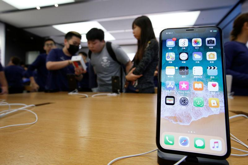 Customers buy iPhone X at an Apple Store in Hong Kong