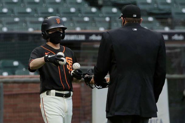 PHOTO: San Francisco Giants ball kid Austin Ginn, left, brings balls to umpire Brian Knight during the first inning of an exhibition baseball game between the Oakland Athletics and the Giants in San Francisco, Tuesday, July 21, 2020. (Jeff Chiu/AP)
