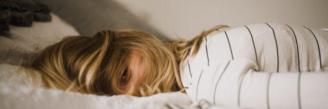 Blonde, white woman laying face down on a bed