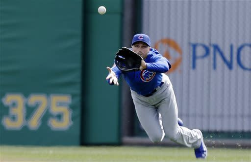 Chicago Cubs right fielder Nate Schierholtz dives for a fly ball hit by Pittsburgh Pirates' Neil Walker to end the second inning of a baseball game in Pittsburgh, Thursday, April 4, 2013. (AP Photo/Gene J. Puskar)