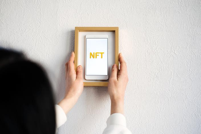Non-fungible token NFT, crypto art, digital art, new type of cryptorurrency. Cell phone with golden NFT text in golden frame as art object.