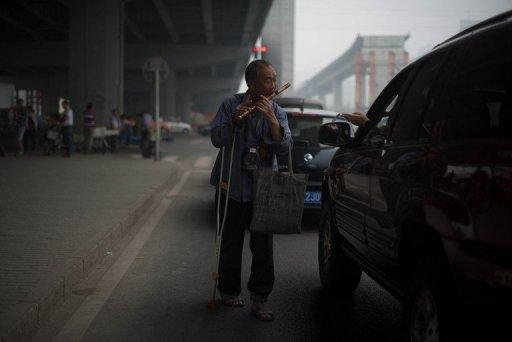 A man plays a flute as a driver holds out money on a road in Beijing on May 24, 2013