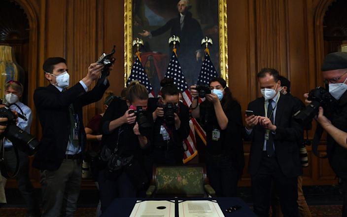 Photographers take pictures of the article of impeachment against US President Donald Trump during an engrossment ceremony - AFP