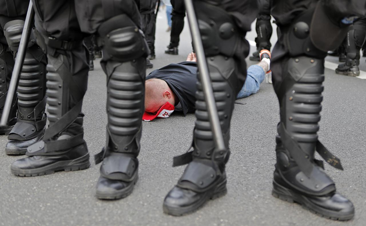 A handcuffed Polish fan lies flat on the street prior to the Euro 2012 soccer championship Group A match between Poland and Russia in Warsaw, Poland, Tuesday, June 12, 2012. Russian soccer fans clashed with police and Poland supporters in separate incidents in Warsaw on Tuesday, just hours before the two teams were to meet in an emotionally charged European Championship match. Several people were injured. (AP Photo/Gero Breloer)
