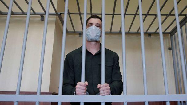 PHOTO: Former Marine Trevor Reed, who was detained in 2019 and accused of assaulting police officers, stands inside a defendants' cage during a court hearing in Moscow, July 30, 2020.  (Maxim Shemetov/Reuters, FILE)
