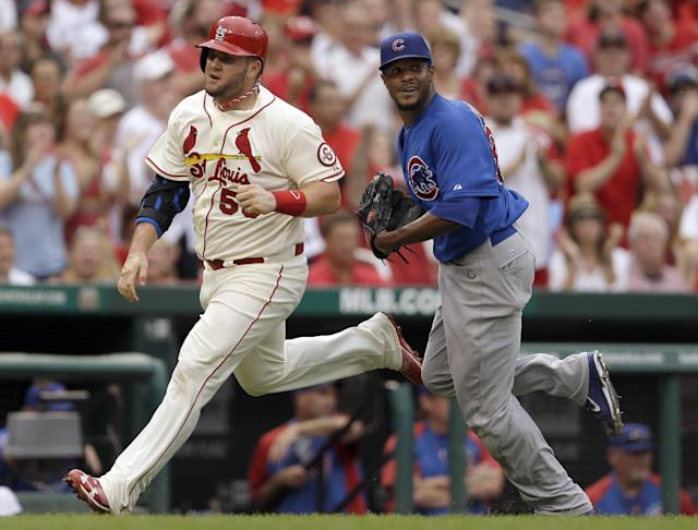 St. Louis Cardinals' Matt Adams, left, heads in to score on a two-run double by Yadier Molina as Chicago Cubs starting pitcher Edwin Jackson, right, runs to back up the throw during the third inning of a baseball game on Saturday, Sept. 28, 2013, in St. Louis. (AP Photo/Jeff Roberson)