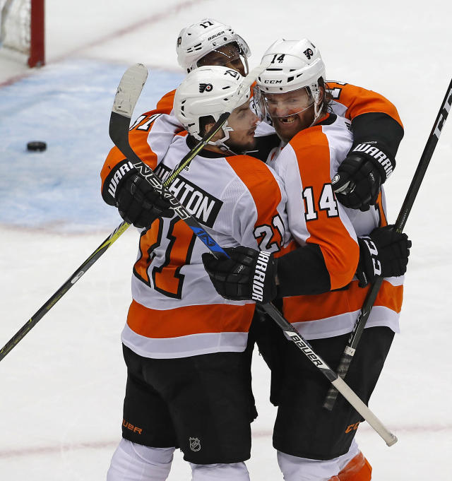 Philadelphia Flyers' Sean Couturier (14) celebrates his goal with Scott Laughton (21) and Wayne Simmonds during the third period in Game 5 of an NHL first-round hockey playoff series against the Pittsburgh Penguins in Pittsburgh, Friday, April 20, 2018. (AP Photo/Gene J. Puskar)