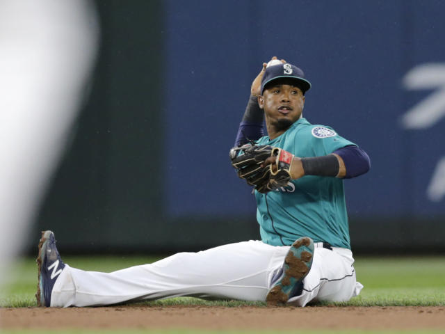 Seattle Mariners shortstop Jean Segura throws the ball to second from the ground to force out Kansas City Royals' Whit Merrifield during the second inning of a baseball game Friday, June 29, 2018, in Seattle. (AP Photo/John Froschauer)