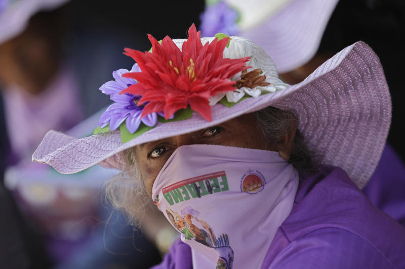 A woman looks at the camera during the Margaridas march, in front of the Brazilian National Congress, in Brasilia, Brazil, Wednesday, Aug. 14, 2019. The Margaridas, or Daisies, formed to honor Margarida Maria Alves, a murdered local leader of the Rural Worker's Union, renowned for surmounting the embedded cultural stereotypes and obstacles for women, especially those working in rural areas. (AP Photo/Eraldo Peres)