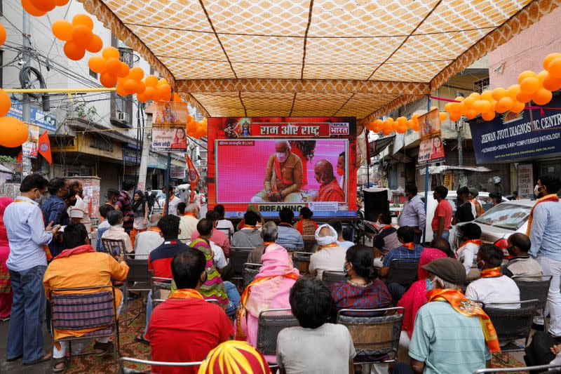 People watch a live screening of the stone laying ceremony of the Ram Temple by Prime Minister Narendra Modi in Ayodhya, in New Delhi