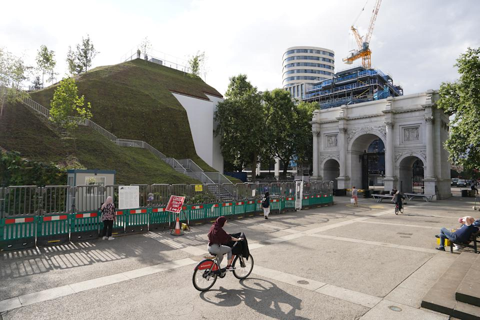 The Marble Arch Mound in central London which has opened to the public. The summit of the new 25-metre high installation will provide sweeping views of Hyde Park, Mayfair and Marylebone when it opens to the public in July. The artificial hill has been built on a scaffolding base, with layers of soil and plywood forming the mound which has a hollow centre with space for exhibitions and displays. Picture date: Tuesday July 27, 2021.