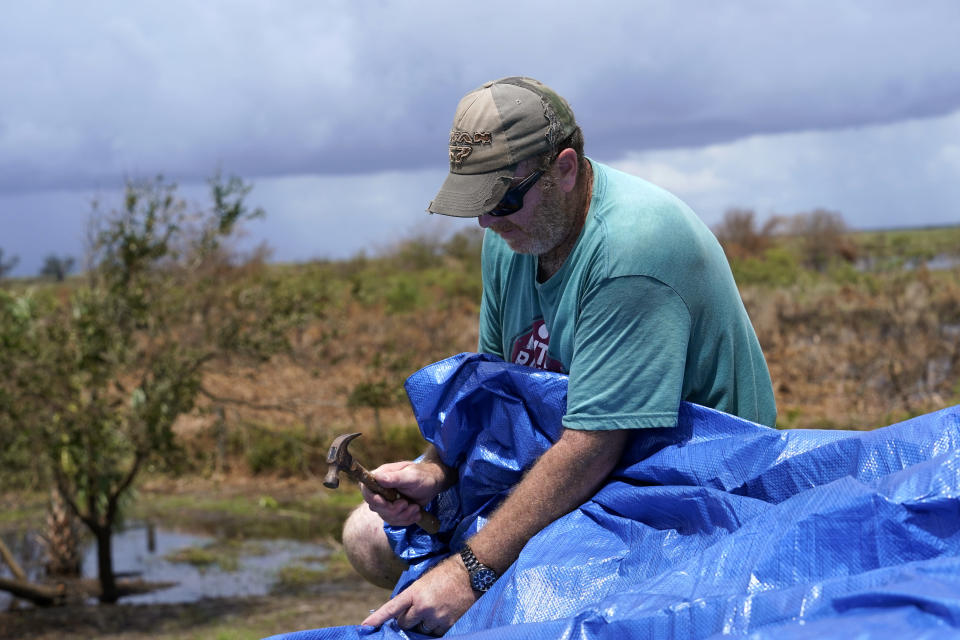 Mark Poindexter puts a tarp on the damaged roof of his home in in Gulf Breeze, La., in the aftermath of Hurricane Laura, Saturday, Aug. 29, 2020. (AP Photo/Gerald Herbert)