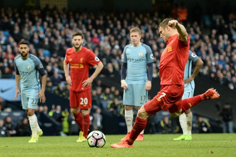 Liverpool's midfielder James Milner (R) scores against Manchester City from the penalty spot on March 19, 2017