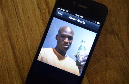 A photo of Aaron Alexis, 34, the suspected shooter who was among 13 people killed in the shooting at Washington Navy Yard, is displayed on the phone of Oui Suthamtewakul owner of the Happy Bowl Asian Restaurant, in White Settlement, Texas September 17, 2013. REUTERS/Tim Sharp