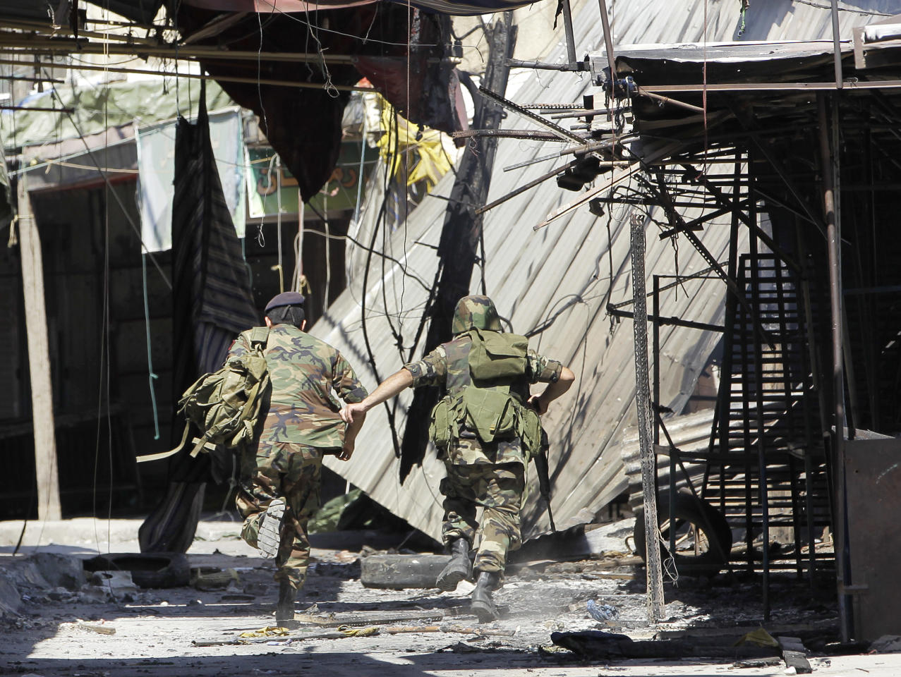 Lebanese army soldiers run from sniping at an outdoor market that was damaged during clashes that erupted between pro and anti-Syrian regime gunmen in the northern port city of Tripoli, Lebanon, Friday, Aug. 24, 2012. The latest round of fighting first erupted on Monday in northern Lebanon and at least 15 have been killed in Tripoli this week and more than 100 have been wounded in fighting that is a spillover from Syria's civil war. (AP Photo/Hussein Malla)