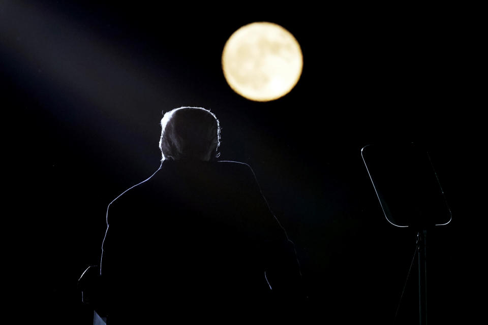 With a full moon in the background, President Donald Trump speaks at a campaign rally at Pittsburgh-Butler Regional Airport, Saturday, Oct. 31, 2020, in Butler, Pa. (AP Photo/Alex Brandon)