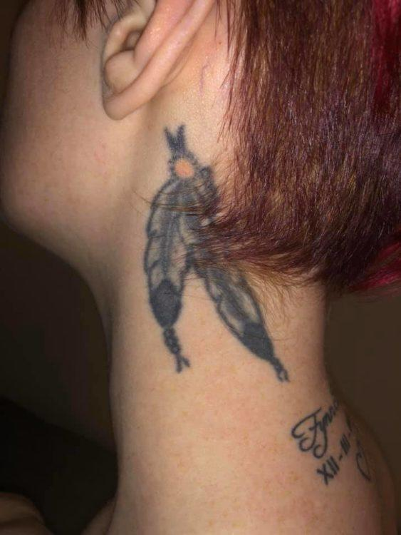 A woman who used to have BD shows off a neck tattoo of two feathers held together by a red bead. The feathers are white with black tips and appear just below the woman's ear.
