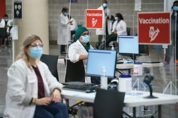 Health-care workers wait for patients at a COVID-19 vaccination clinic in Montreal's Olympic Stadium on Tuesday.