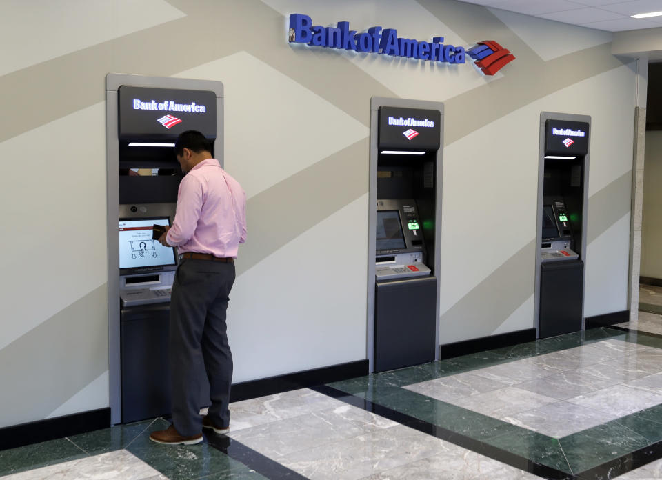 FILE- In this July 9, 2018, file photo a customer makes a transaction at a Bank of America ATM at the company's headquarters in Charlotte, N.C. Bank of America Corp. reports earnings Monday, Oct. 15. (AP Photo/Chuck Burton, File)