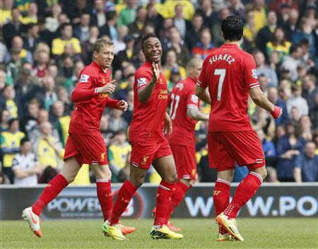 Liverpool's Raheem Sterling (C) celebrates his goal against Norwich City with teammates Lucas Leiva (L) and Luis Suarez during their English Premier League soccer match at Carrow Road in Norwich April 20, 2014. REUTERS/Stefan Wermuth