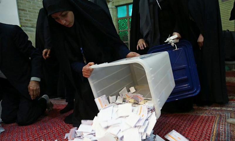 Poll workers empty ballot boxes after the election comes to an end in Tehran.