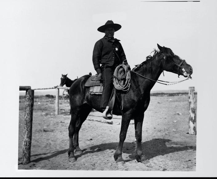 An African American cowboy sits saddled on his horse in Pocatello. At the crossing of the Oregon Short Line and the Utah and Northern railroads, Pocatello attracted non-Mormon workers, including Idaho's first African Americans.