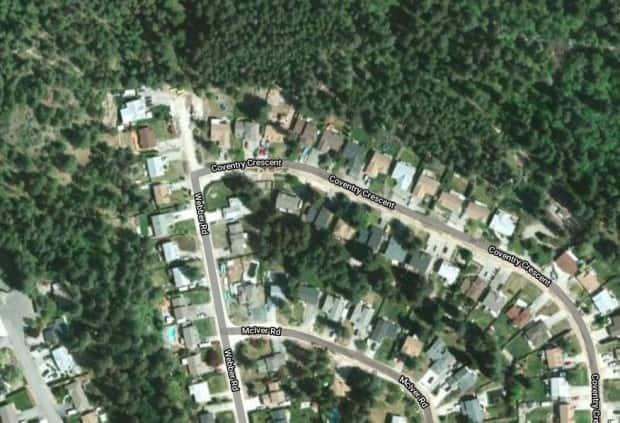 RCMP say a suspect was arrested after someone tried to start a fire on the wooded hillside near these homes in West Kelowna on Saturday evening.  (Google Maps - image credit)