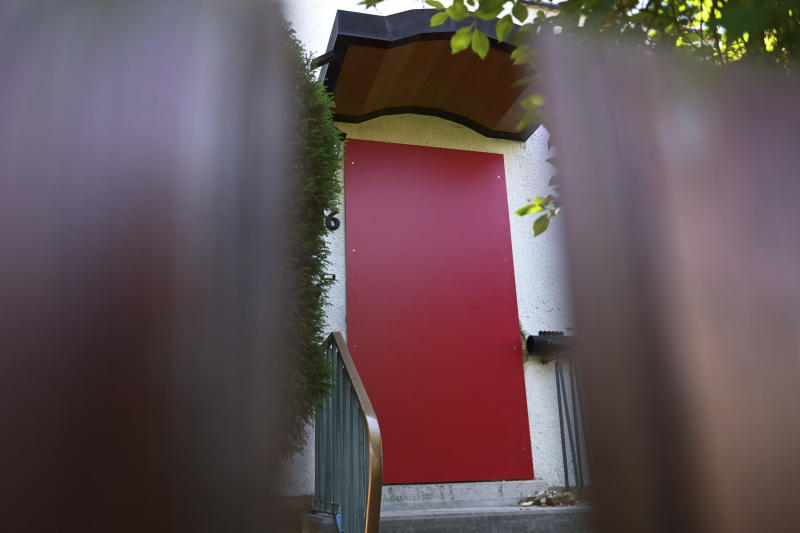 In this picture taken trough a fence the entrance of a house of a suspect in a homicide case is pictured in Kassel, Germany, Tuesday, June 18,2019. Police on Saturday arrested a 45-year-old known far-right extremist with a string of convictions for violent crimes dating back decades. The regional government offical Walter Luebcke, a long-time member of Chancellor Angela Merkel's center-right Christian Democrats, was found shot in the head on June 2 at his home near the central German city of Kassel. (Uwe Zucchi/dpa via AP)