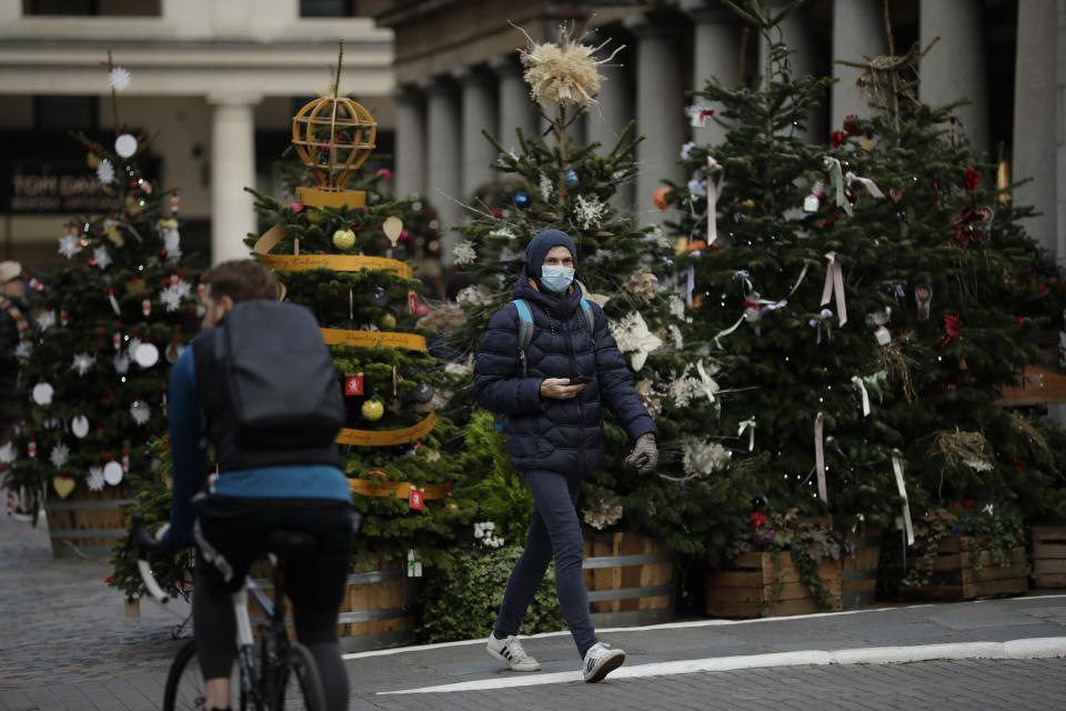 A man wearing a face mask walks past Christmas trees in Covent Garden, during England's second coronavirus lockdown in London, Thursday, Nov. 26, 2020. As Christmas approaches, most people in England will continue to face tight restrictions on socializing and business after a nationwide lockdown ends next week, the government announced Thursday. (AP Photo/Matt Dunham)