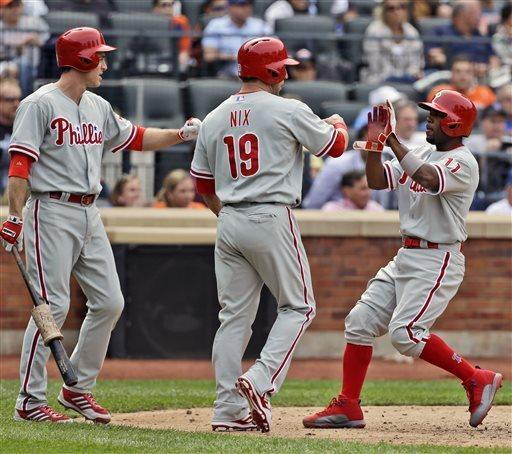 Philadelphia Phillies' Jimmy Rollins, right, is greeted by teammates Laynce Nix, center, and Chase Utley after he and Nix scored on a double hit by Ryan Howard during the seventh inning of the baseball game against the New York Mets at Citi Field, Sunday, April 28, 2013, in New York. (AP Photo/Seth Wenig)
