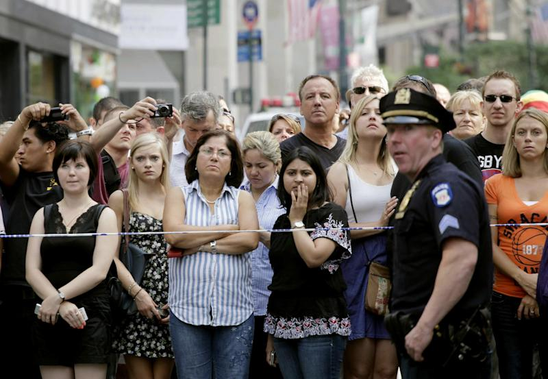 Bystanders and a police officer stand on Fifth Avenue to view the scene after a multiple shooting outside the Empire State Building, Friday, Aug. 24, 2012, in New York. At least four people were shot on Friday morning and the gunman was dead, New York City officials said. A witness said the gunman was firing indiscriminately. Police said as many as 10 people were injured, but it is unclear how many were hit by bullets. A law enforcement official said the shooting was related to a workplace dispute. The official spoke on condition of anonymity because the investigation was ongoing.  (AP Photo/Mark Lennihan)