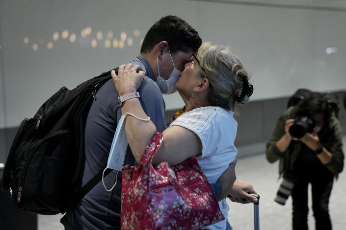 Karen Tyler greets and kisses her son Jonathan, who she's not seen for over a year and a half as he arrives on a flight from Houston, Texas, in the U.S., at Terminal 5 of Heathrow Airport in London, Monday, Aug. 2, 2021. Travelers fully vaccinated against coronavirus from the United States and much of Europe were able to enter Britain without quarantining starting today, a move welcomed by Britain's ailing travel industry. (AP Photo/Matt Dunham)