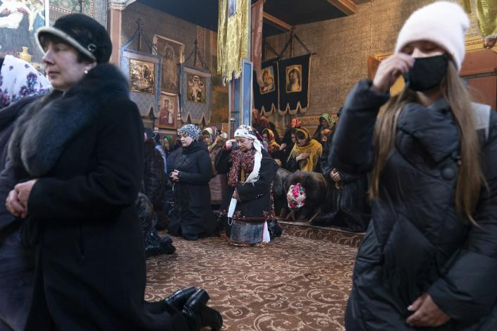"Dr. Viktoria Mahnych, wearing a Hutsul's traditional colorful clothes, center, crosses herself holding a face mask in her hand because other worshippers forced her to take off her mask "" in order not to remind about the contagion"" in the Holy Trinity church during the Orthodox Christmas celebration in Iltsi village, Ivano-Frankivsk region of Western Ukraine, Thursday, Jan. 7, 2021. Mahnych fears that a lockdown in Ukraine came too late and the long holidays, during which Ukrainians frequented entertainment venues, attended festive parties and crowded church services, will trigger a surge in new coronavirus infections. (AP Photo/Evgeniy Maloletka)"