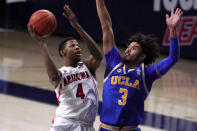 Arizona guard Dalen Terry (4) shoots over UCLA guard Johnny Juzang during the first half of an NCAA college basketball game, Saturday, Jan. 9, 2021, in Tucson, Ariz. (AP Photo/Rick Scuteri)