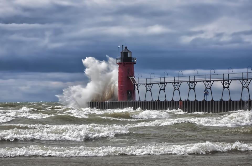 Waves crash against the pier in South Haven