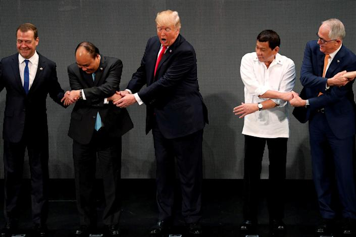 "Trump registers his surprise as he realizes other leaders, including Russia's Prime Minister Dmitry Medvedev, Vietnam's Prime Minister Nguyen Xuan Phuc, President of the Philippines Rodrigo Duterte and Australia's Prime Minister Malcolm Turnbull, are crossing their arms for the traditional ""ASEAN handshake"" as he participates in the opening ceremony of the ASEAN Summit in Manila, Philippines, on Nov. 13."